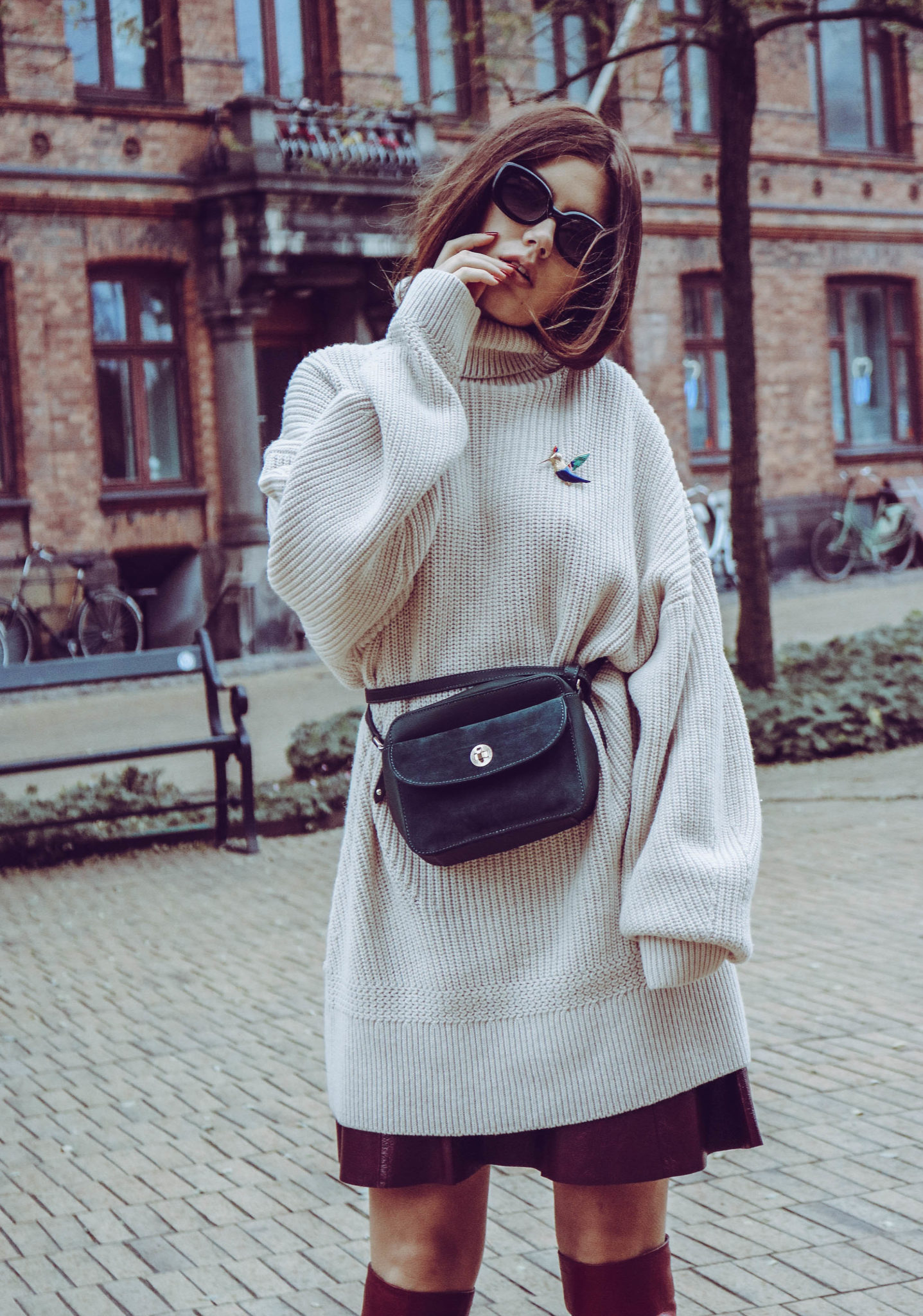 oversized knitwear, high boots, and bumbag