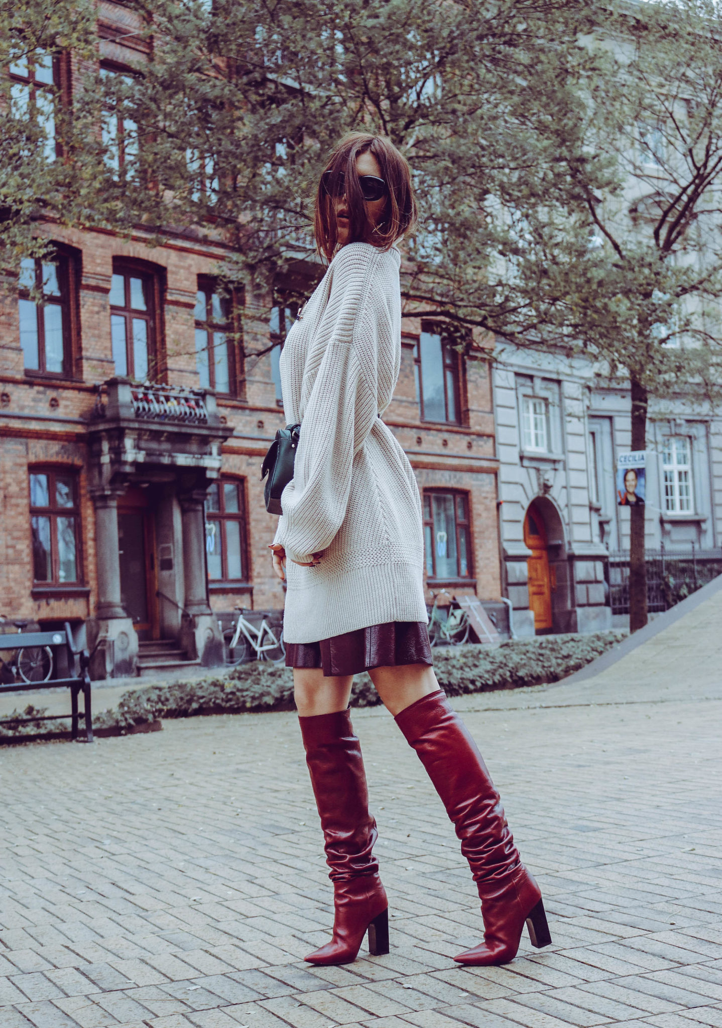 oversized knitwear, high boots and bumbag